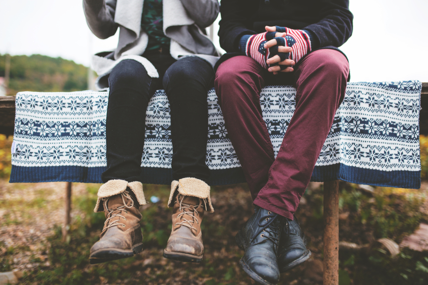a couple in warm clothes sitting on a picnic table