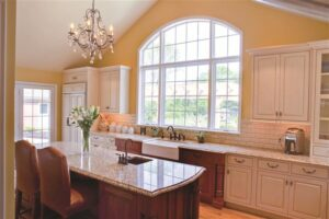 Beautiful large, arched-top window with grids over upscale kitchen sink