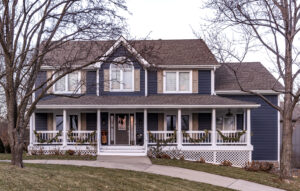 Large two-story farmhouse with dark blue lap siding and white trim